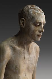 lifelike wood sculptures of pensive and