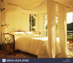 Tall Canopy Bed by White Awning And Drapes Above Bed With White Bedlinen In White