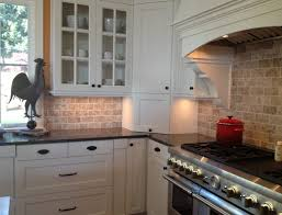 contemporary tumbled stone kitchen backsplash of brown cabinets