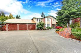 big luxury house with tree car garage view of entrance and