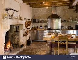 lit fire in fireplace in country kitchen with rustic wooden table