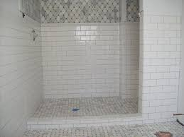 marble tile shower floor with ceramic subway tile on the walls