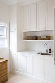 all white laundry room features white shaker cabinets adorned with