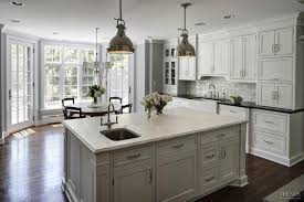 white kitchen with granite and marble countertops and subway tile