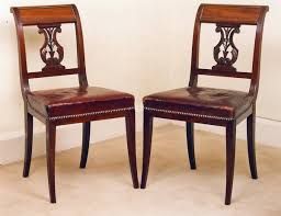 pair of mahogany sabre legged chairs with ornamental back carvings