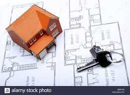 a model home and house key on architectural floor plans for an