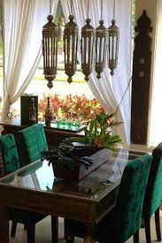 moroccan dining room with green chairs and moroccan lanterns