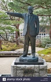 a statue of adachi zenko stands in the famous gardens of the