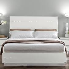 low profile white wooden bed with high head board combined with