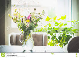 bouquet of flowers in a glass vase on table in front of a window