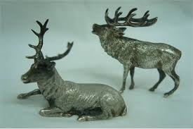two silver stag ornaments one lying and one baying