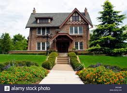 brick home front view of english tudor style with blooming gardens