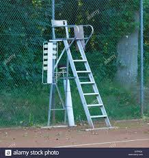 old tennis umpire chair on a red tennis court