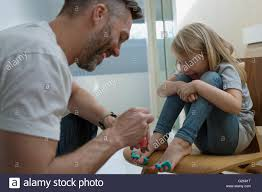 father painting daughters toenails with nail polish stock photo