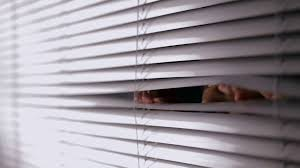 cu man opening blinds and looking out stock video footage