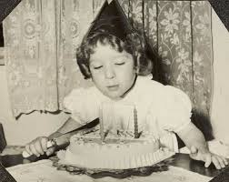 digital photograph in party hat blowing out candles at