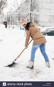 woman shoveling snow in parking in cold day in winter stock photo