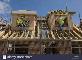 builders working on dormer windows on the roof of a new house