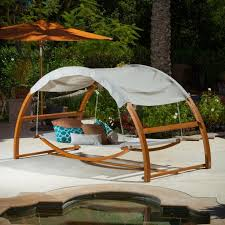 exterior round wicker daybed with curved canopy tent and red