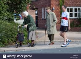 two elderly people out on a sunday morning and runner walking to