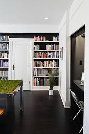 love the floor to ceiling bookshelf black on white interiors