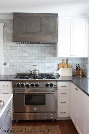 kitchen style stainless steel gas range hood and white subway