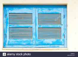 blue wooden window shutters with vents in white stone wall