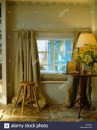lighted l on small antique table beside window with heavy linen