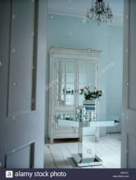 door open to mirrored glass table and white cupboard with glazed