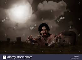 zombie rising from graveyard halloween concept stock photo