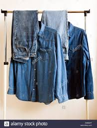 selection of denim shirt and jeans on clothes hanging rail stock