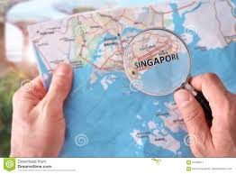 Singapore On Map Man Consulting A Map Of Singapore With A Magnifying Glass Stock