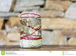 jar decorated with roses and lace on a stone background home
