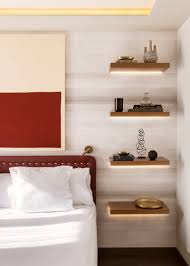 bedroom design idea replace a bedside table and lamp with in this modern bedroom four floating wood shelves with hidden lighting have been installed