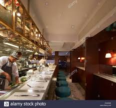open kitchen with bar counter seating and chefs at work the