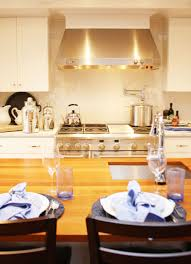 pot filler faucet with range hood and white kitchen cabinet also