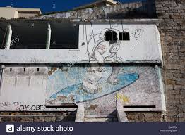 surfing mural painting wall stock photos surfing mural painting astronaut on surfboard surfing the space mural on an old abandoned building in estoril