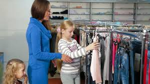 with two daughters shopping for clothes in a clothing