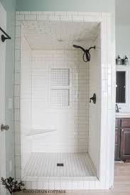 white subway tiles frame a gray marble herringbone tiled shower