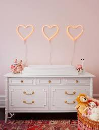 heart shaped marquee lights over white bamboo dresser changing