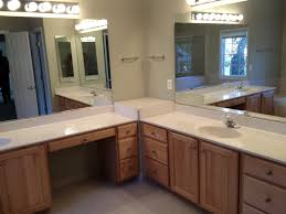 brown wooden bathroom vanity with white top and large mirror on