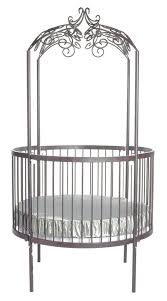 round shape wrought iron baby crib behind metal crib with iron art