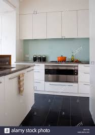 black floor tiles in modern white kitchen with glass splash back