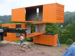 cranes positioning a house made of recycled shipping containers