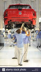 vw saveiro workers stand underneath a vw saveiro cross on the assembly line