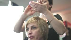 hairstyle for evening event beautiful blonde in a barber shop stylist makes hair young girl