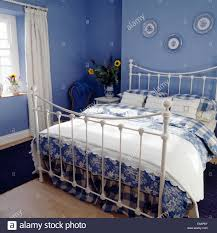 blue white bedlinen on white wrought iron bed in blue bedroom