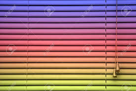 closed rainbow colored blinds showing adjusting cords and slats
