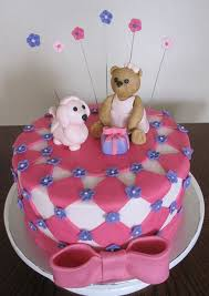round pink birthday cake for girls with pink bow and teddy bear