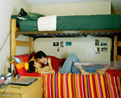 young couple embracing in dormitory bedroom side view stock photo